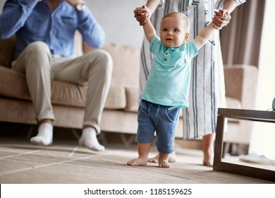 Happy family -Smiling baby boy learning walking with mother, child enjoys the first steps