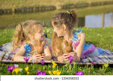 Happy family, smiling children. Kids hold Easter chocolate bunny, talk and laugh. Easter holidays, family holidays, joy and spring concept.