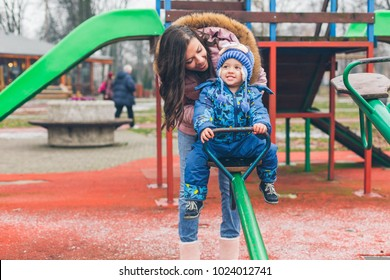 Happy family. Smiling little boy and his mom having fun at playground
