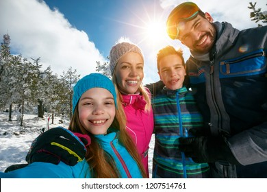 Happy family smiling and making selfie on winter ski vacation