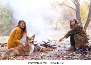 Happy family - smiling mom, daughter and dog on picnic in the autumn forest