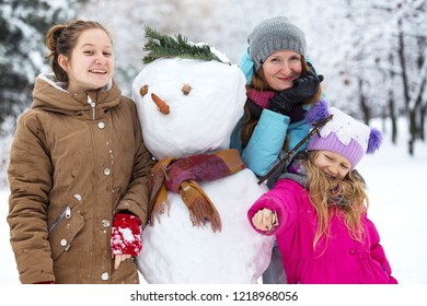 happy family - smiling mother and daughters with snowman at the winter day