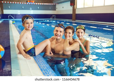 A happy family is smiling in a swimming pool.