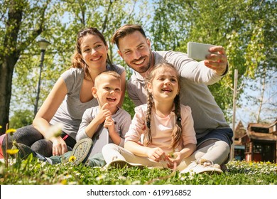 Happy family smiling while taking self-portrait  in park.
