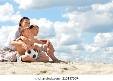 Happy family with soccer ball on beach in summer day