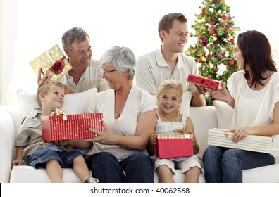 Happy family in sofa giving presents for Christmas