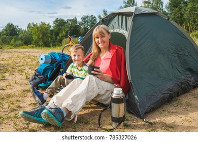 Happy family (son and mother) drinking tea and sitting in tent on nature.