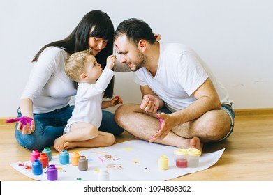 happy family son with parents and a cat painting a poster and one another with paints