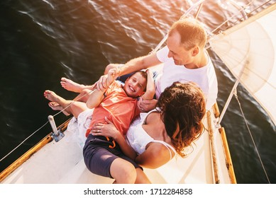 Happy family with son resting on a sailing yacht