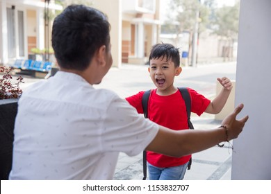 Happy family son running and hugging dad after going back from school