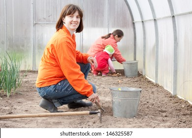 Happy family sows seeds in soil at greenhouse