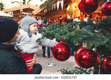 Happy family spend time at a Christmas street market fair in the old town of Salzburg, Austria. Holidays, Christmas, Family concept. Mother and son at winter outdoor among Christmas decorations