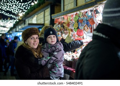 Happy family spend time at a Christmas street market fair in the old town. Holidays, Christmas, Family concept. Mother and son at winter outdoor among Christmas decorations