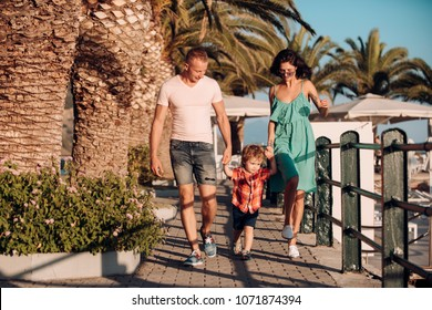 Happy family spend time together, urban background. Parents with son walking near palm trees, happy boy with smiling face. Mother and father with their child on sunny day. Family walk concept.