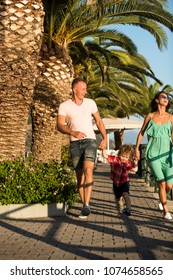 Happy family spend time together, urban background. Mother, father with child laughing on sunny day. Parents with son walking near palm trees, happy boy with smiling face. Family walk concept.