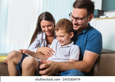 Happy family spending time at home and looking something fanny on tablet.