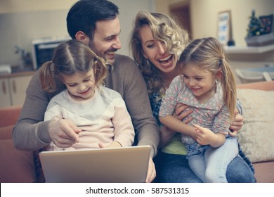 Happy family spending time at home and looking on the laptop.