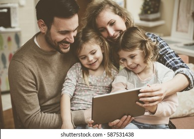 Happy family spending time at home and looking on the digital tablet.