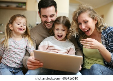 Happy family spending time at home and looking something fanny on laptop.