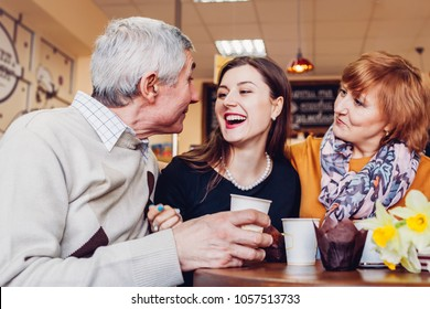 Happy family spending time together. Senoir family couple with adult daughter chat and laugh in cafe. Family values