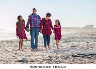 Happy family spending time together outdoors walking on the beach holding hands interacting.