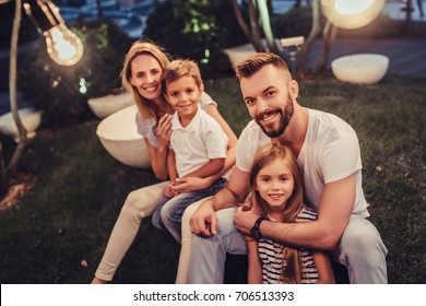 Happy family is spending time together in park in the evening with garland of light bulbs. Parents with children are having fun and enjoying being together. Mom, dad, son and daughter outdoors.