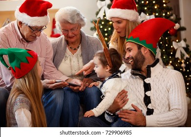 Happy family is spending time together on Christmas day and using tablet