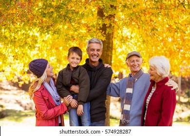 Happy family standing against trees at park during autumn