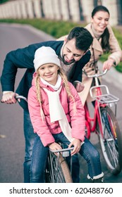 Happy family standing with bicycles and smiling at sunny autumn day