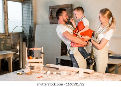 Happy family standing in carpentry workshop hugging each other. Dad took his son in his arms standing next to mom