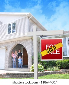 A happy family is standing in front of a home with a For sale sign with a sold sticker on top. There is an exterior image of the hose with clouds in the background.