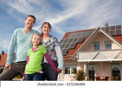 Happy family standing in front of house with solar panels