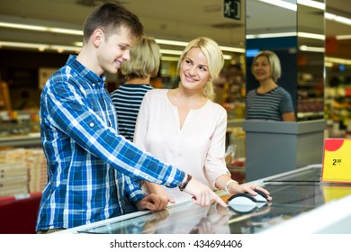 Happy family standing near display with frozen food in supermarket. Focus on the woman