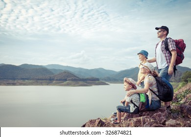 Happy family standing near the lake at the day time.  Concept of friendly family.