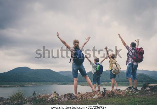 Gelukkige familie staat in de buurt van het meer op de dag tijd. Concept van vriendelijke familie.