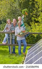 Happy family standing near solar panel holding garden vegetables