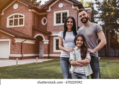 Happy family is standing near their modern house, smiling and looking at camera.