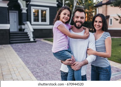 Happy family is standing near their modern private house, smiling and looking at camera.