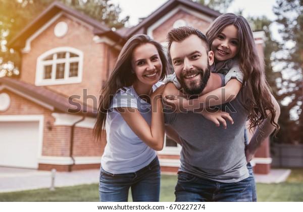 Die glückliche Familie steht in der Nähe ihres modernen Hauses, lächelt und sieht die Kamera an.