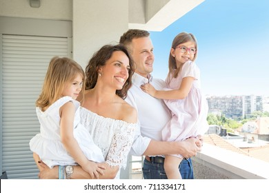 Happy family standing on apartment, hotel, balcony