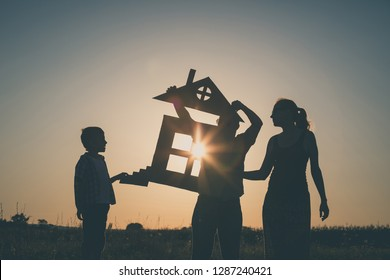 Happy family standing on the field at the sunset time. They build a house. Concept of friendly family.