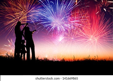 happy family standing on the hill and watching the fireworks