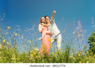 Happy family standing on meadow in summer under a clear blue sky