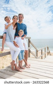 happy family  standing on a wood pontoon in front of the sea in summertime