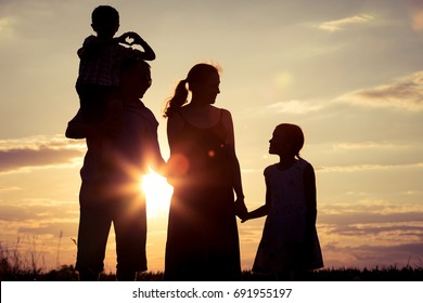 Happy family standing in the park at the sunset time. People having fun outdoors. Concept of friendly family.