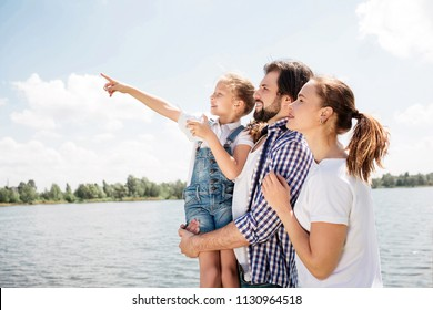 Happy family is standing together and looking up. Guy is holding hi daughter. Girl is pointing up and forward. Woman is standing besides her husband.