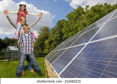 Happy family standing together near large solar panels
