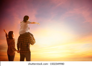 happy family standing and watching the sunset