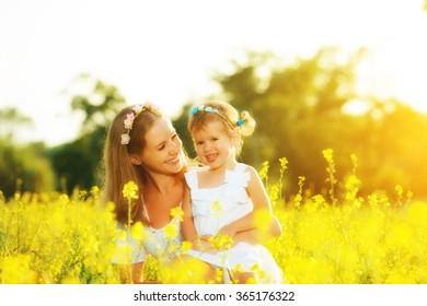 happy family in the summer meadow, mother embrace little daughter girl child with yellow flowers