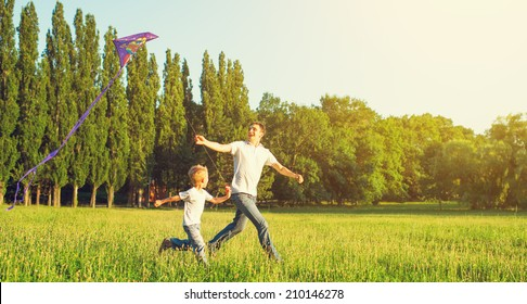 happy family in summer nature. Dad and son child flying a kite